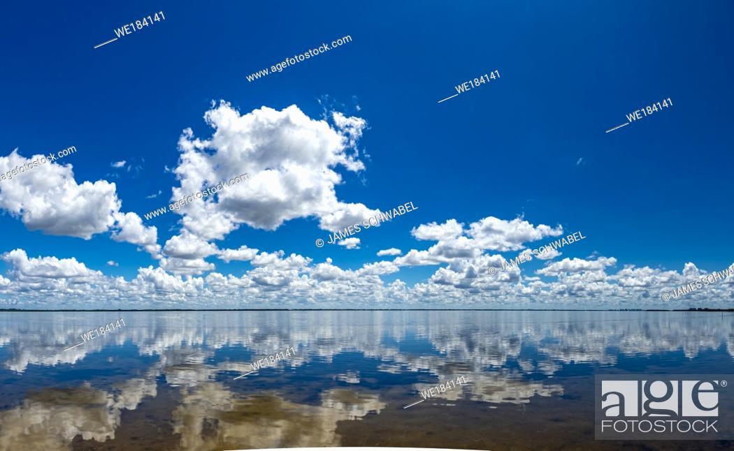 Imagen: White clouds in blue sky reflecting in Sarasota Bay taken from Longboat Key in Southwestern Florida.