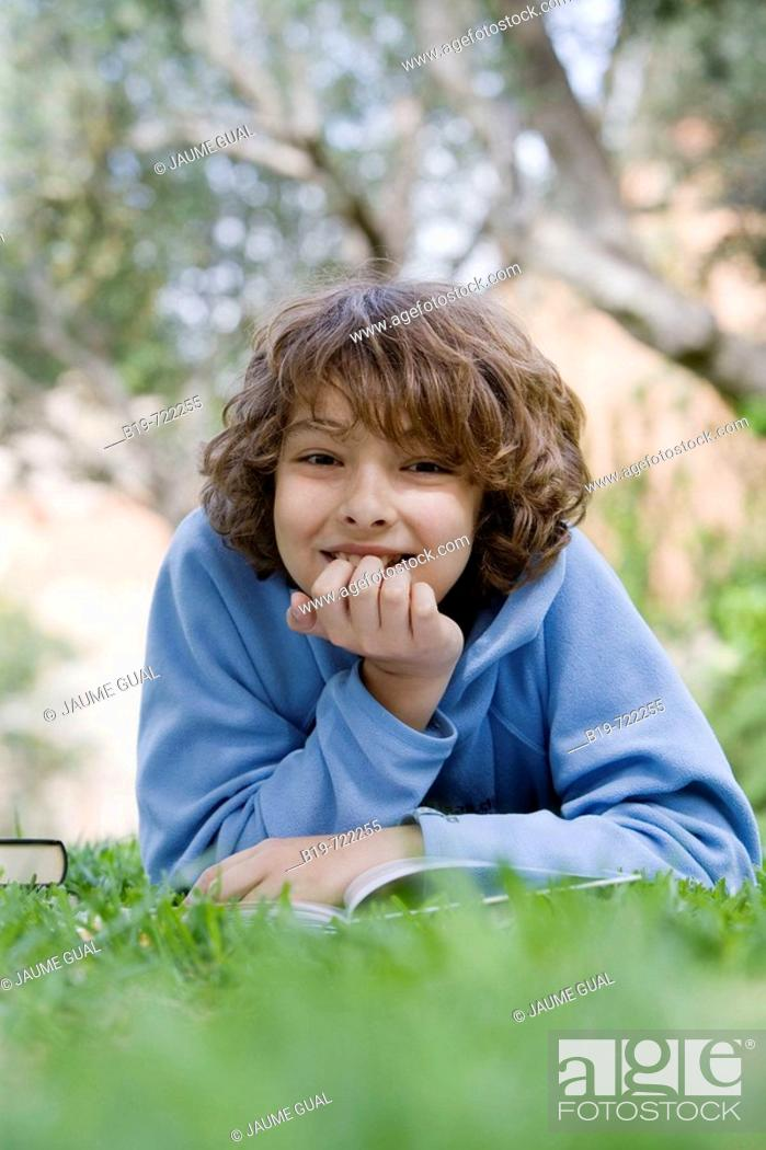Stock Photo: Boy laying on grass reading a book.
