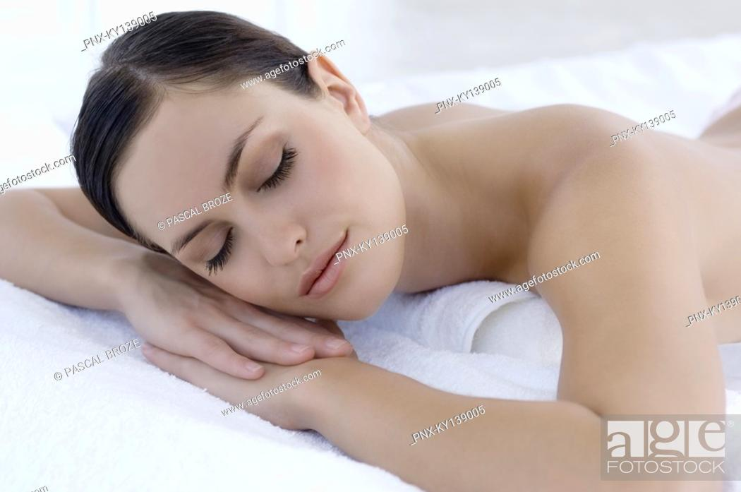 Stock Photo: Young woman sleeping in bed, indoors.