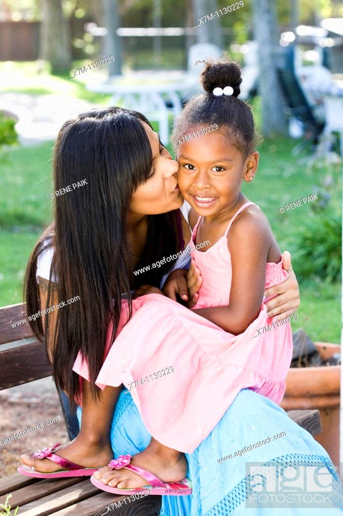 Stock Photo: A mixed race mother kisses her smiling daughter on the cheek.