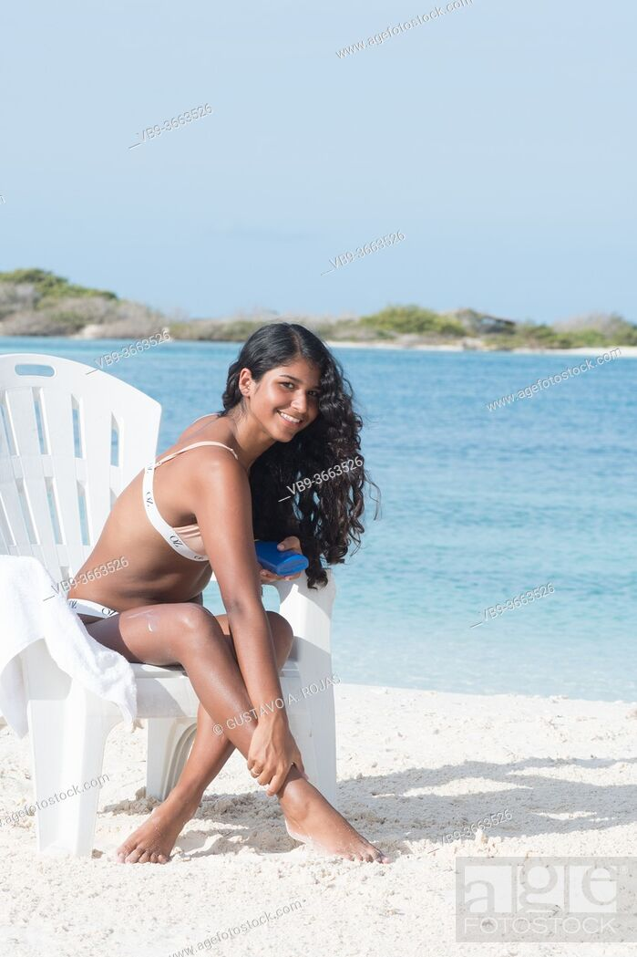 Stock Photo: YOUNG African American WOMAN applying Sunscreen Lotion on legs at Caribbean Beach on the beach chair.