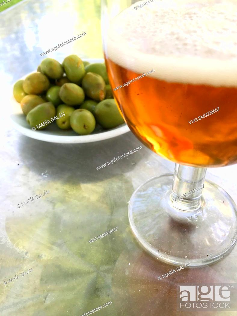 Stock Photo: Glass of beer and green olives. Spain.