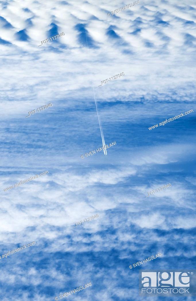 Stock Photo: Plane vapor trail over cloudscape.