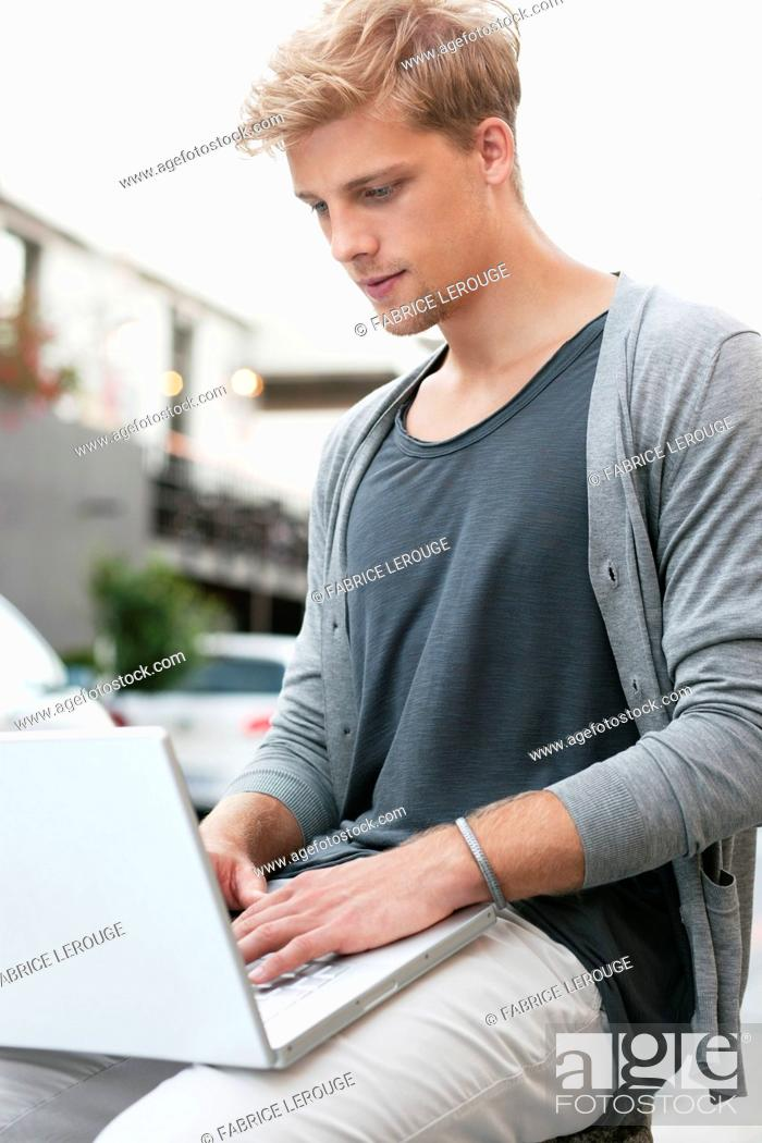 Stock Photo: Young man using a laptop.