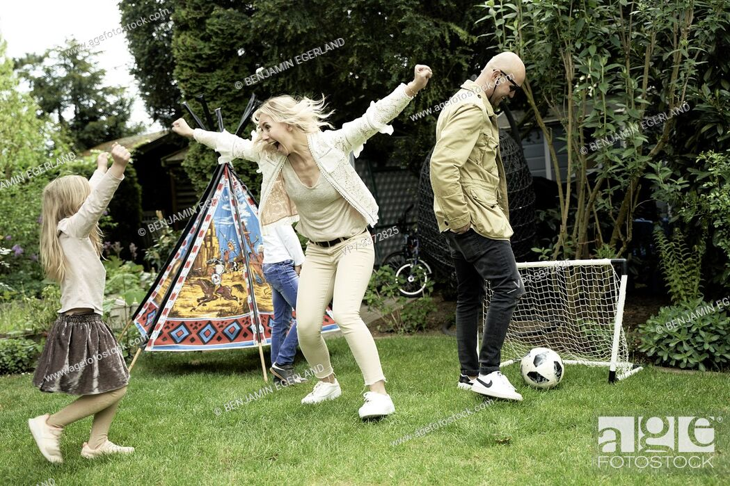 Stock Photo: Family playing soccer in garden.