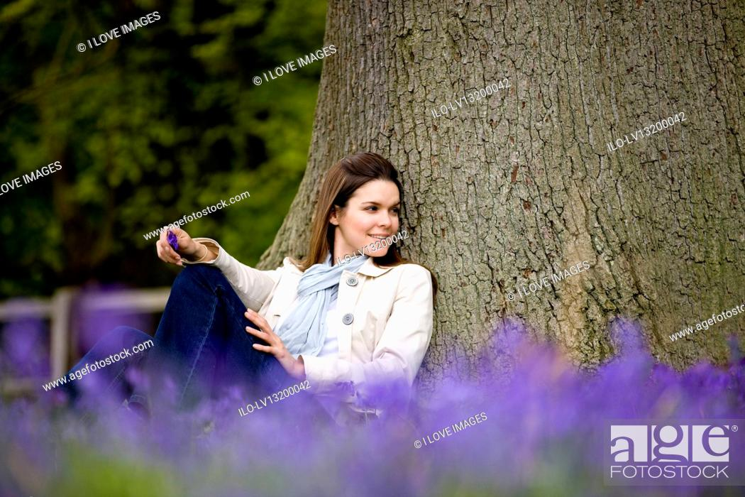 Stock Photo: A young woman leaning against a tree, smiling.