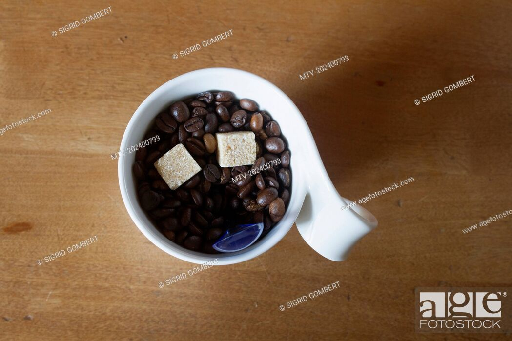 Stock Photo: Close-up of coffee beans with smiley face in cup on wooden table.
