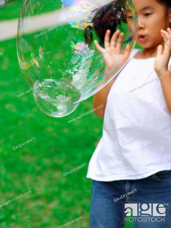 Imagen: Girl standing in a garden and watching a soap bubble.