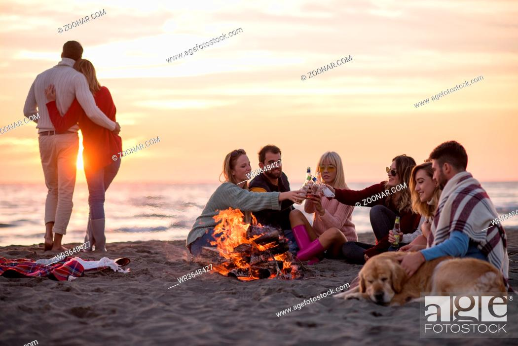 Stock Photo: Young Couple enjoying with friends Around Campfire on The Beach At sunset drinking beer.