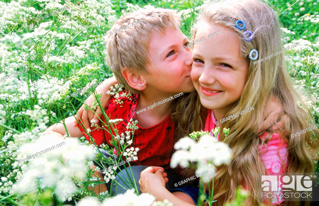 Stock Photo: Young boy kissing a young girl.