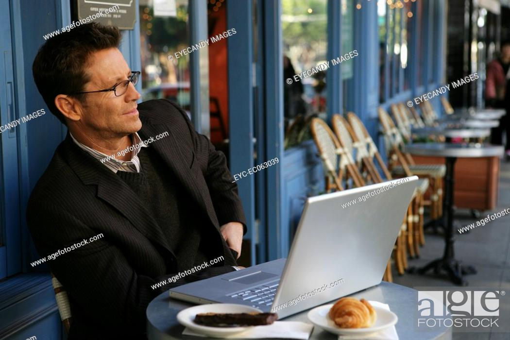 Stock Photo: Mature busines man at a cafe.