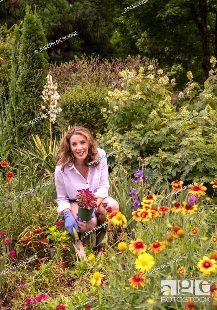 Stock Photo: A pretty 37 year old redheaded woman in a garden setting surrounded by annual and perennial plants in the early summer.