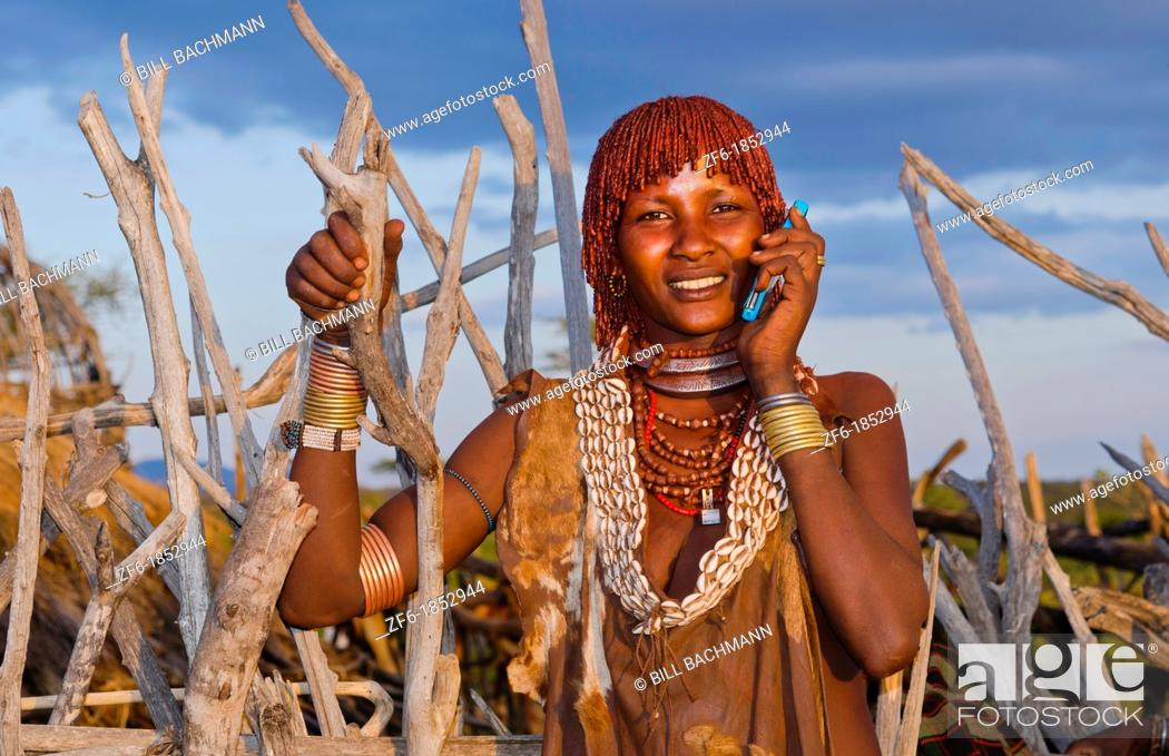 Stock Photo: Turmi Ethiopia Africa Lower Omo Valley village with Bena tribe First Wife smiling with jewelry in wild wood camp hut 24.