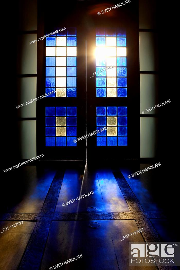 Stock Photo: Blue color projected onto floor through stained glass door.