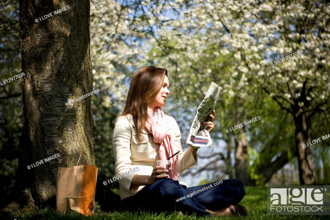 Stock Photo: A young woman having lunch, reading a newspaper.