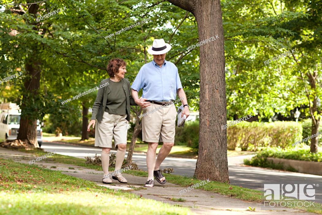 Stock Photo: Senior couple walking in neighborhood.