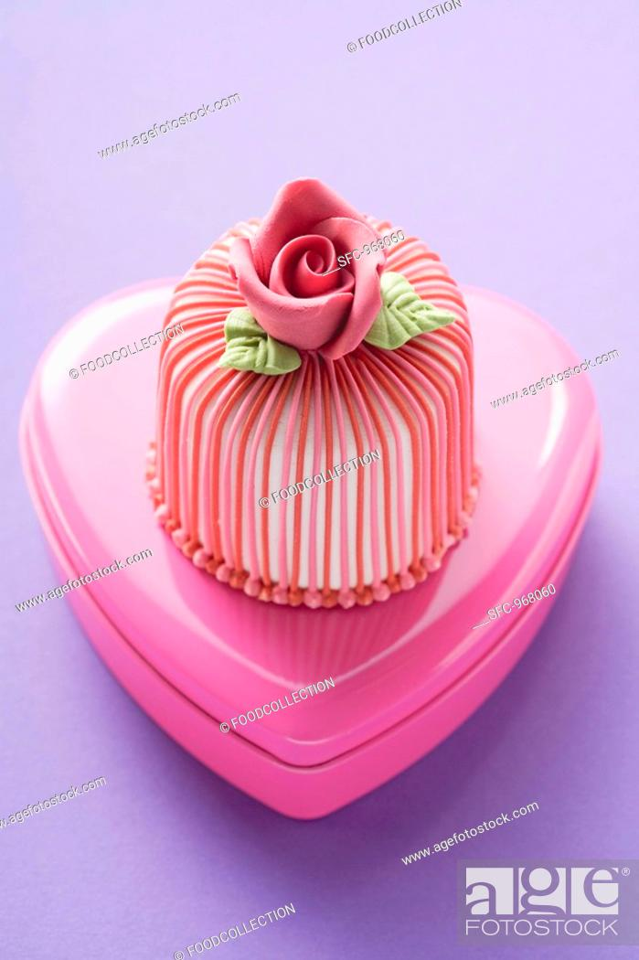 Photo de stock: Marzipan-covered cake on pink chocolate box.