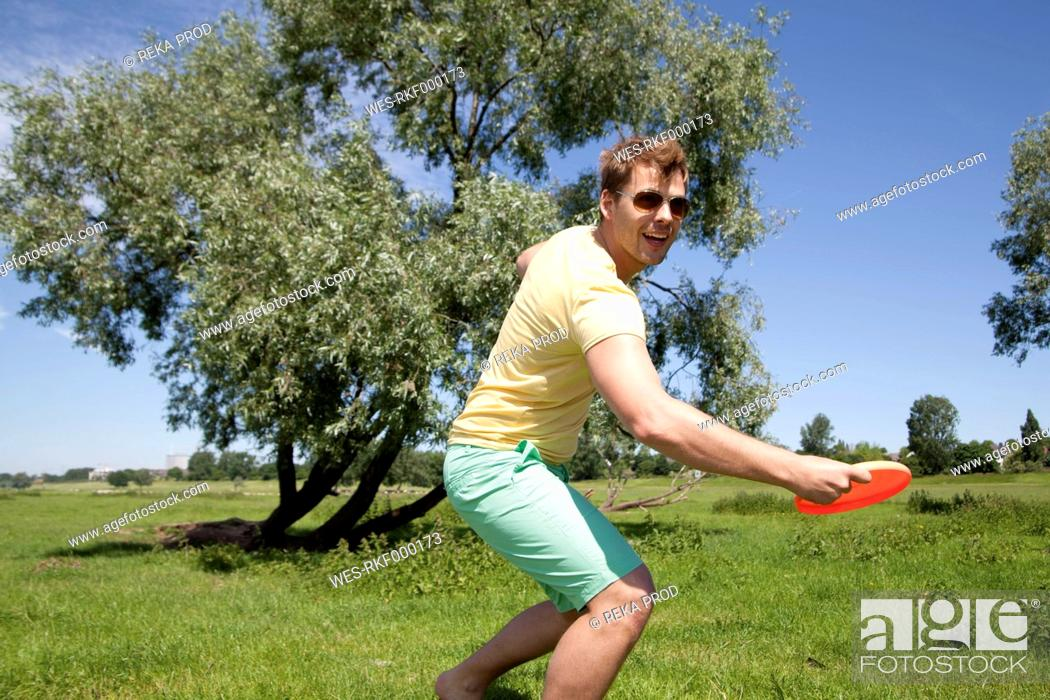 Stock Photo: Germany, North Rhine Westphalia, Duesseldorf, Mid adult man playing with frisbee, smiling.