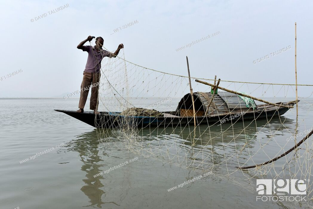 Stock Photo: Fisherman cleaning plastics and other materials from their fishing net after fish in the Brahmaputra river in Guwahati, Assam on Tuesday, 19 February, 2019.