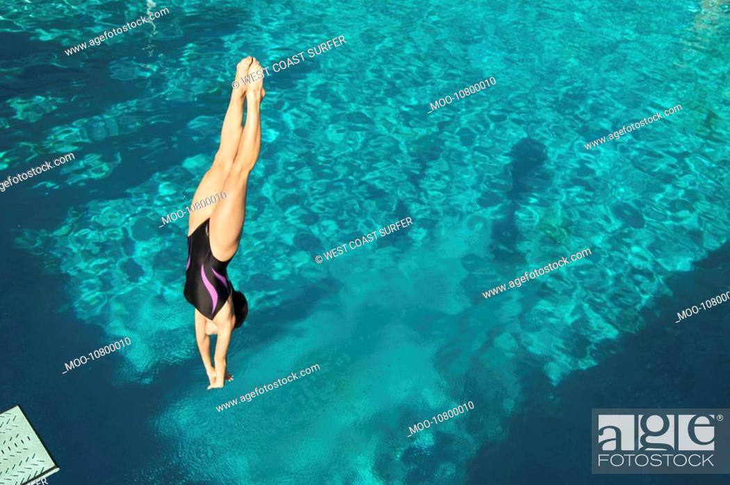 Stock Photo: Female diver diving into pool mid air.
