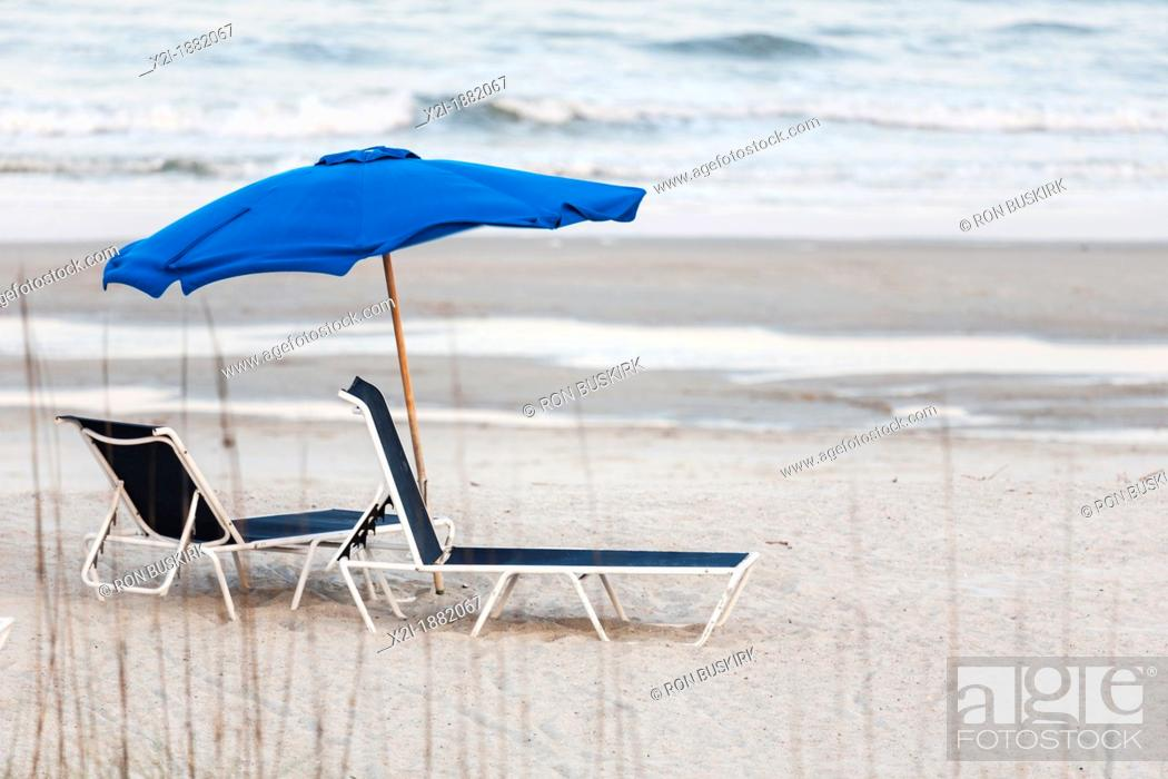 Stock Photo: Empty beach lounge chairs under beach umbrella at Amelia Island, Florida.