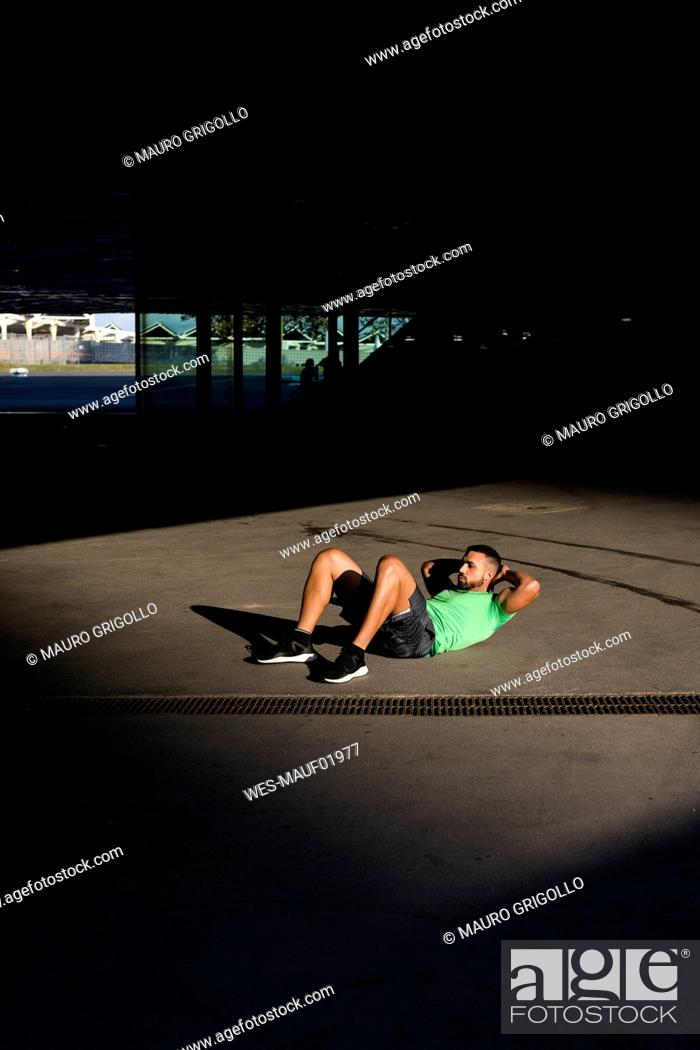 Stock Photo: Sportive man during workout, sit-up.
