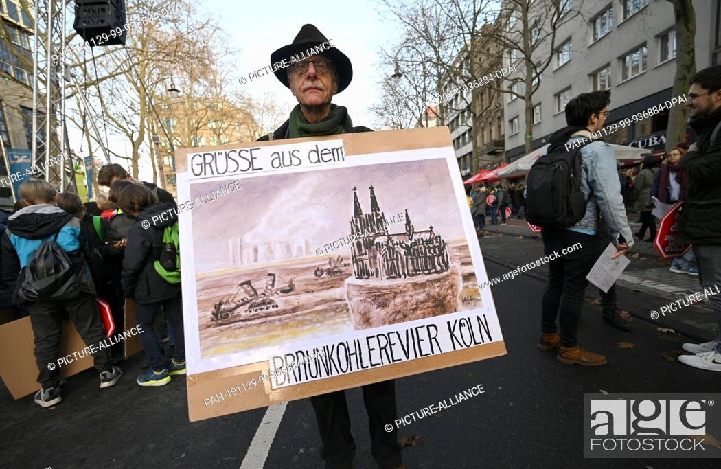 """Stock Photo: 29 November 2019, North Rhine-Westphalia, Cologne: At a demonstration for climate protection, a man stops in front of a sign with the inscription """"""""Greetings."""