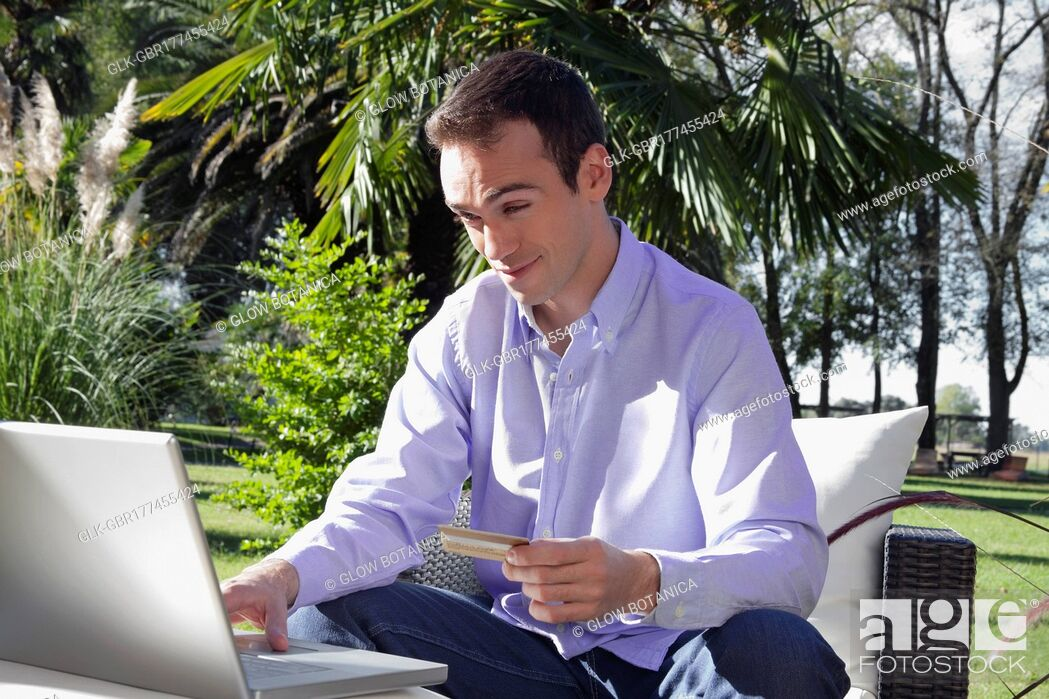 Stock Photo: Man holding a credit card and using a laptop.