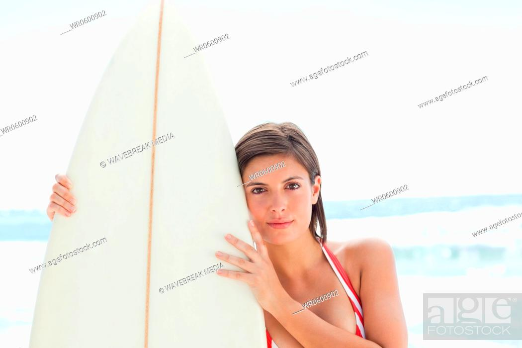 Stock Photo: Woman with a serious expression holding a surfboard.