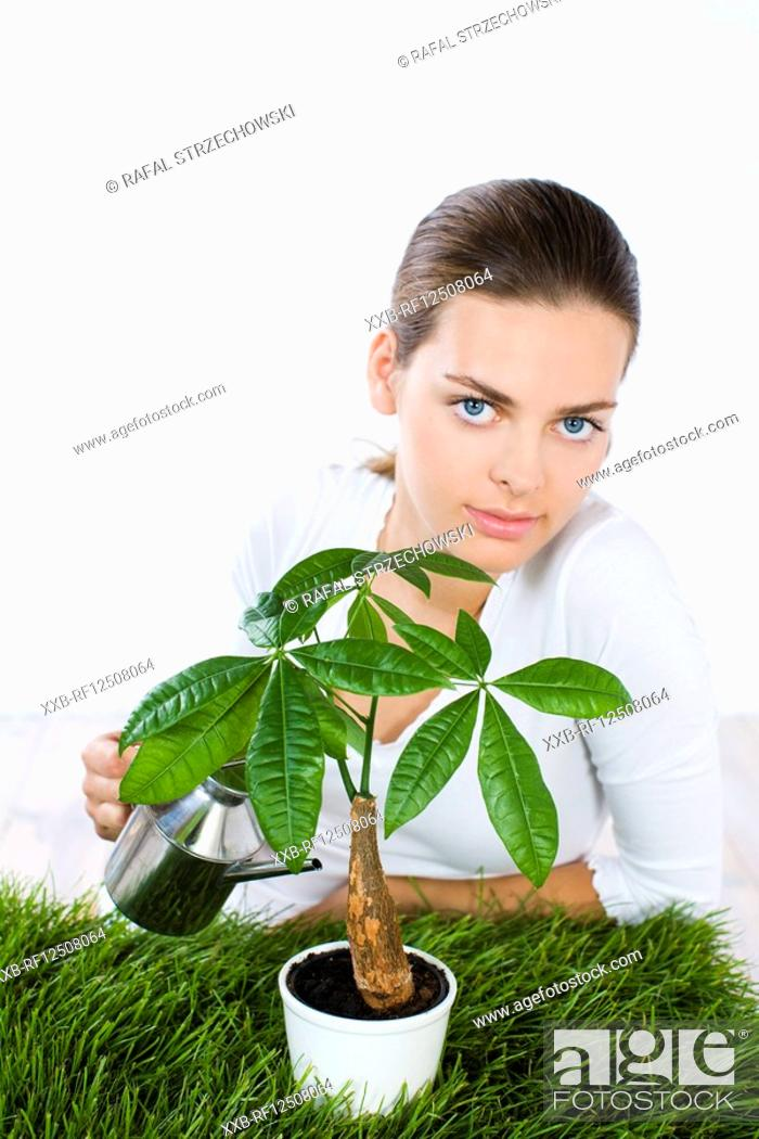 Imagen: young woman watering plant.