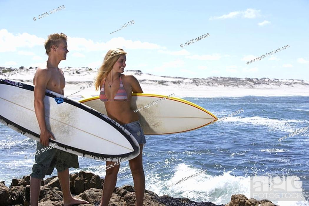 Stock Photo: South Africa, young couple standing on rock beside sea, carrying surfboards under arm, smiling.