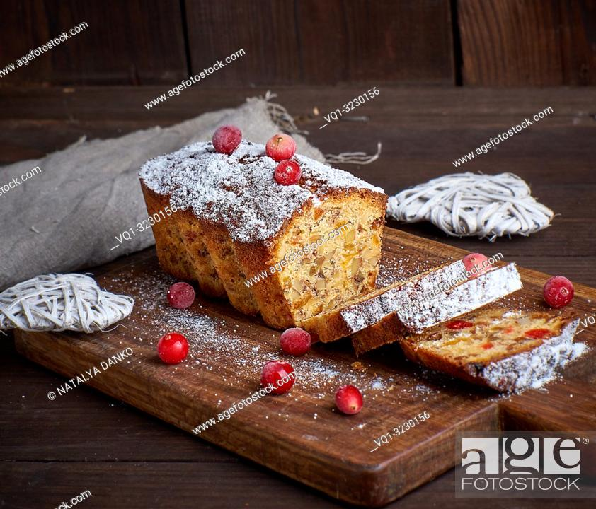 Imagen: traditional Christmas cake stollen cut into pieces on a brown wooden board.