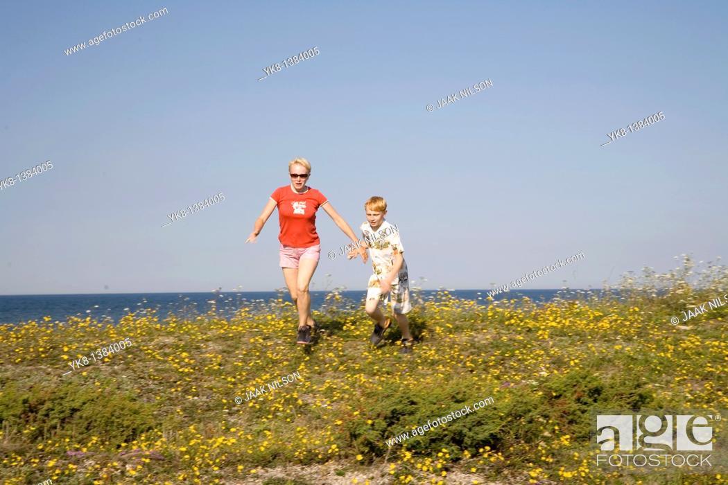 Stock Photo: Woman and Kid Running Hand in Hand on Saaremaa Coast, Saare County, Estonia.