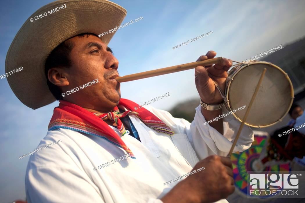 Stock Photo: A Totonacan indigenous man plays flute and drums from Papantla, Veracruz, as part of the Dance of the Guaguas at the pilgrimage to Our Lady of Guadalupe.
