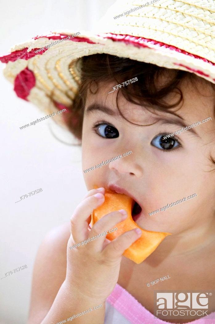Stock Photo: Little girl eating fruit.