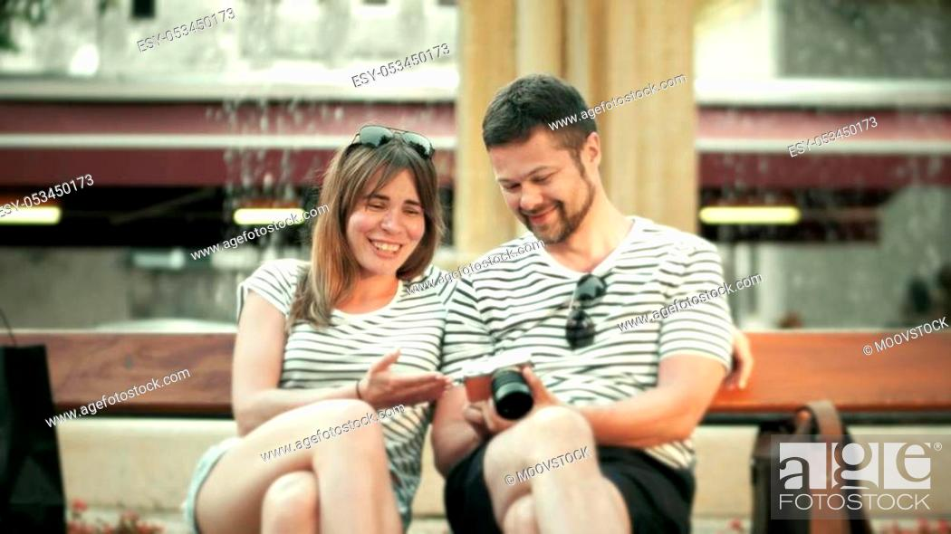 Stock Photo: Young happy couple watching photos in the compact camera.