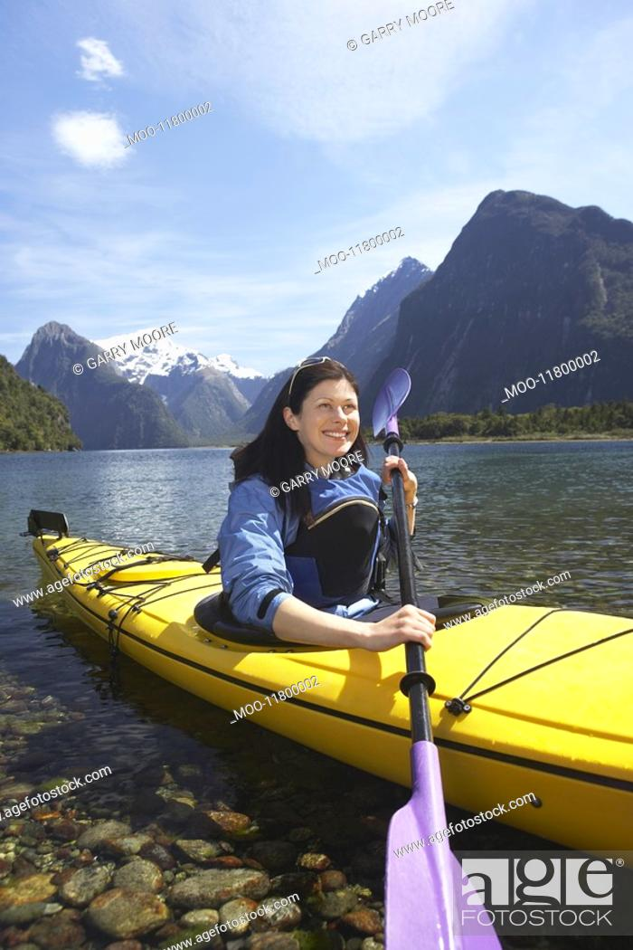 Stock Photo: Woman paddling kayak in mountain lake.