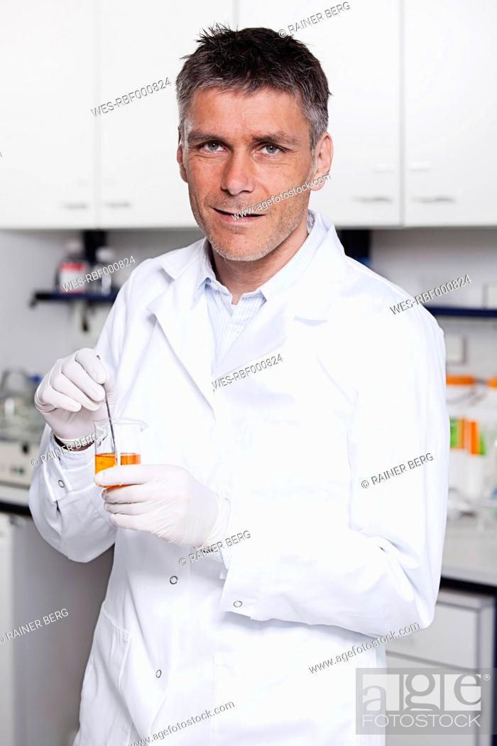 Stock Photo: Germany, Bavaria, Munich, Scientist with liquid in beaker for medical research in laboratory.