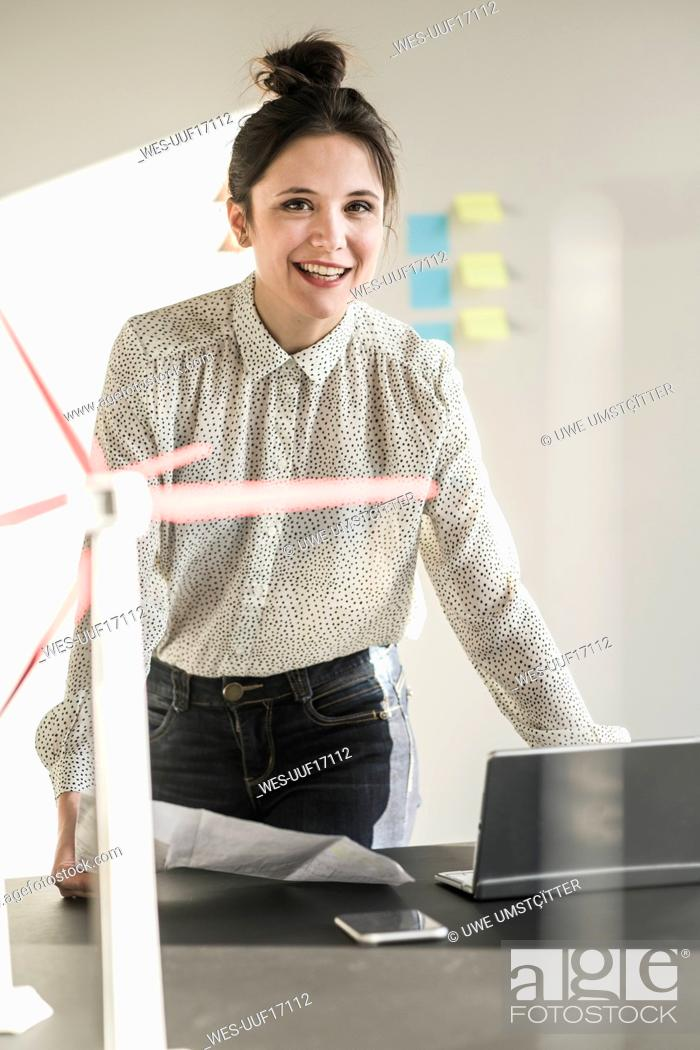 Stock Photo: Portrait of smiling businesswoman with wind turbine model on desk in office.