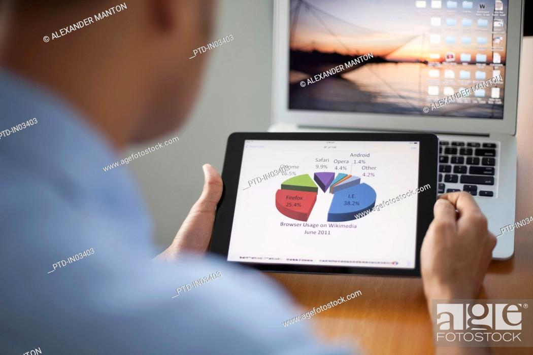 Stock Photo: Singapore, Businessman looking at pie chart on digital tablet.