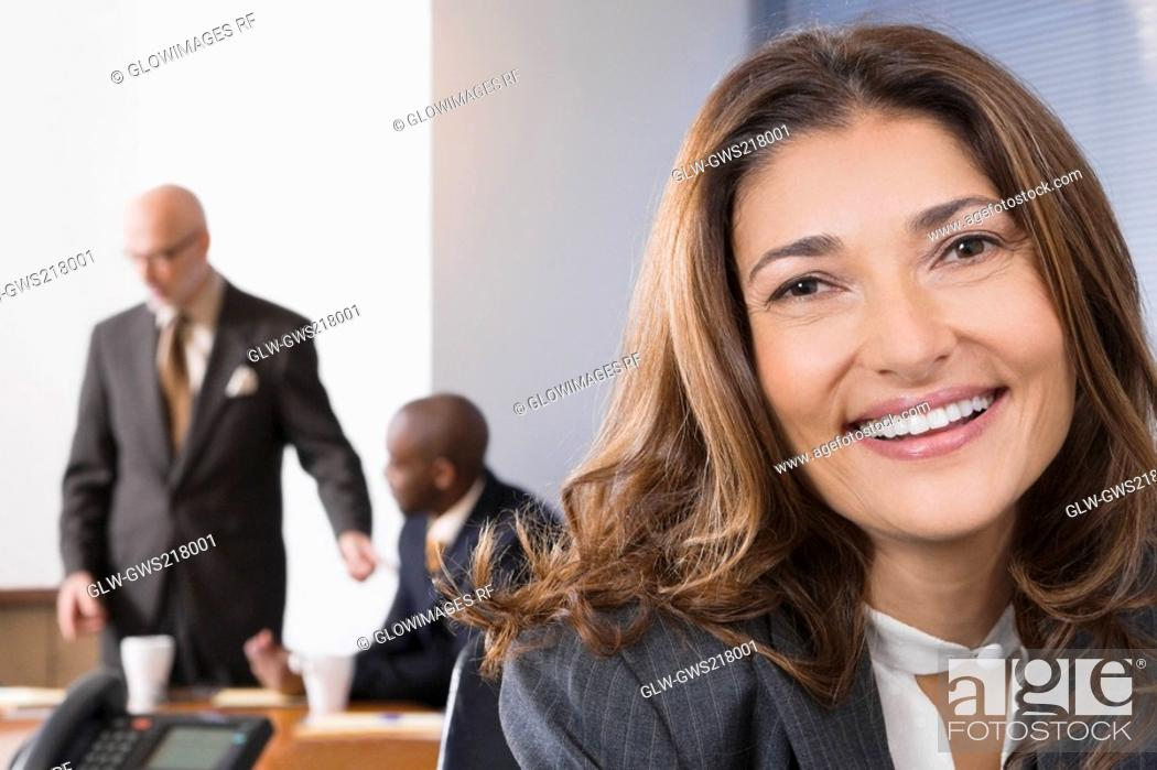 Stock Photo: Portrait of a businesswoman with her colleagues in the background.