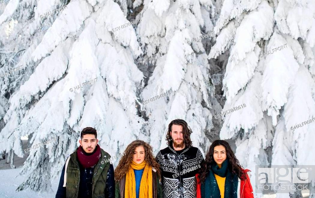 Stock Photo: A group of young cheerful friends on a walk outdoors in snow in winter, looking at camera.