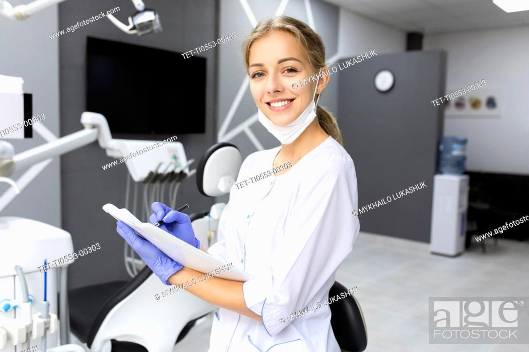 Stock Photo: Dental assistant writing notes.