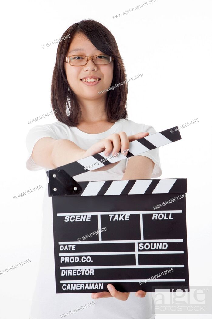 Imagen: Teenage girl holding film slate and smiling at the camera.