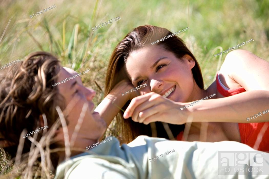 Stock Photo: A young couple lying on the grass.