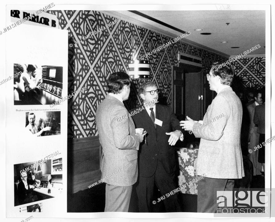 Imagen: Campaign for Johns Hopkins Candid Shot, Three unidentified men standing by a Hopkins Display at the Greebrier, 1983.