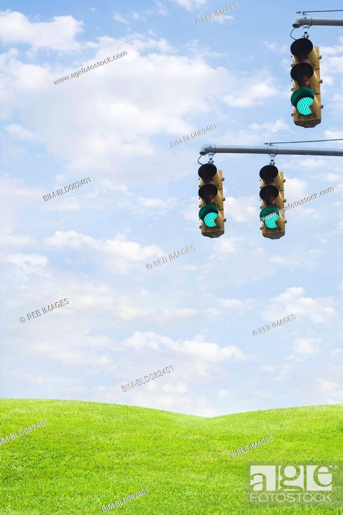 Stock Photo: Green traffic lights over grass field.