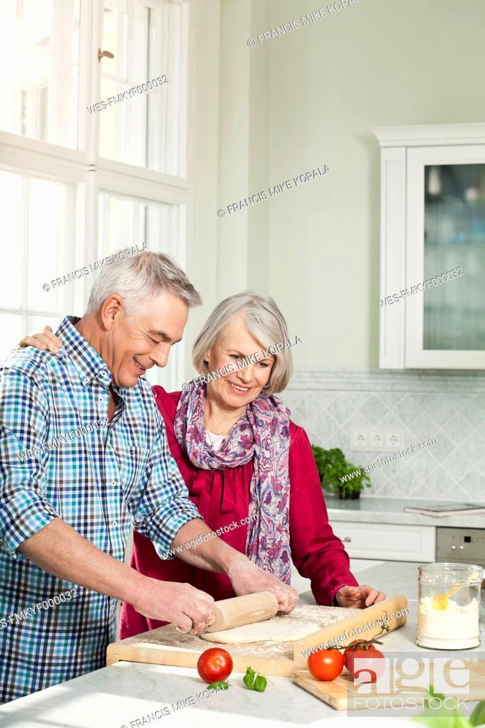 Stock Photo: Germany, Berlin, Man and woman preparing food, smiling.