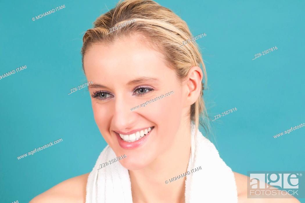 Stock Photo: Beautiful young Caucasian woman with a white towel smiling.