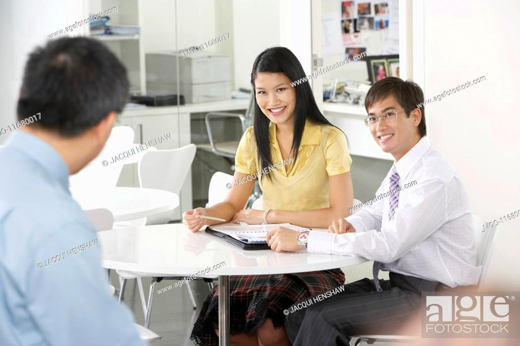 Stock Photo: Two office workers sitting at table in office smiling at colleague.